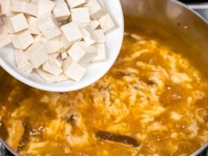 tofu being added to hot and sour soup