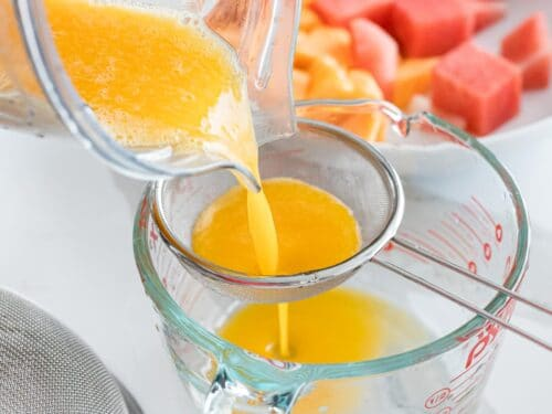 mango juice poured into a strainer