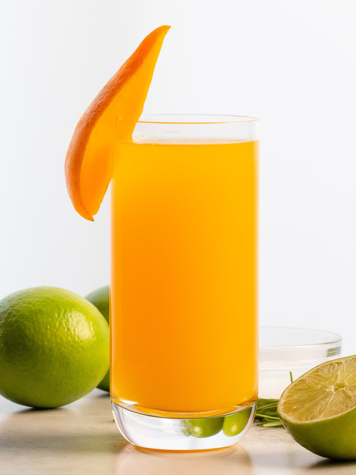 glass of mango agua fresca with lime on the side