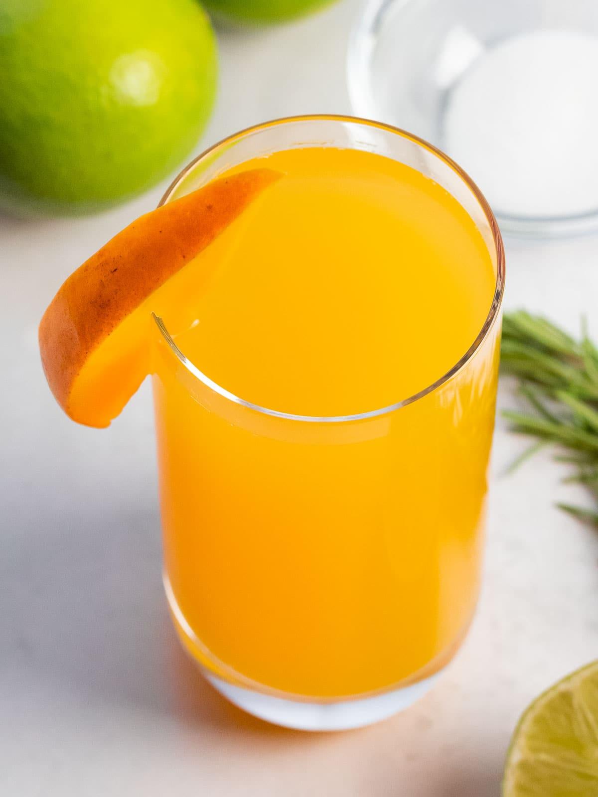 glass of mango agua fresca with a slice of mango