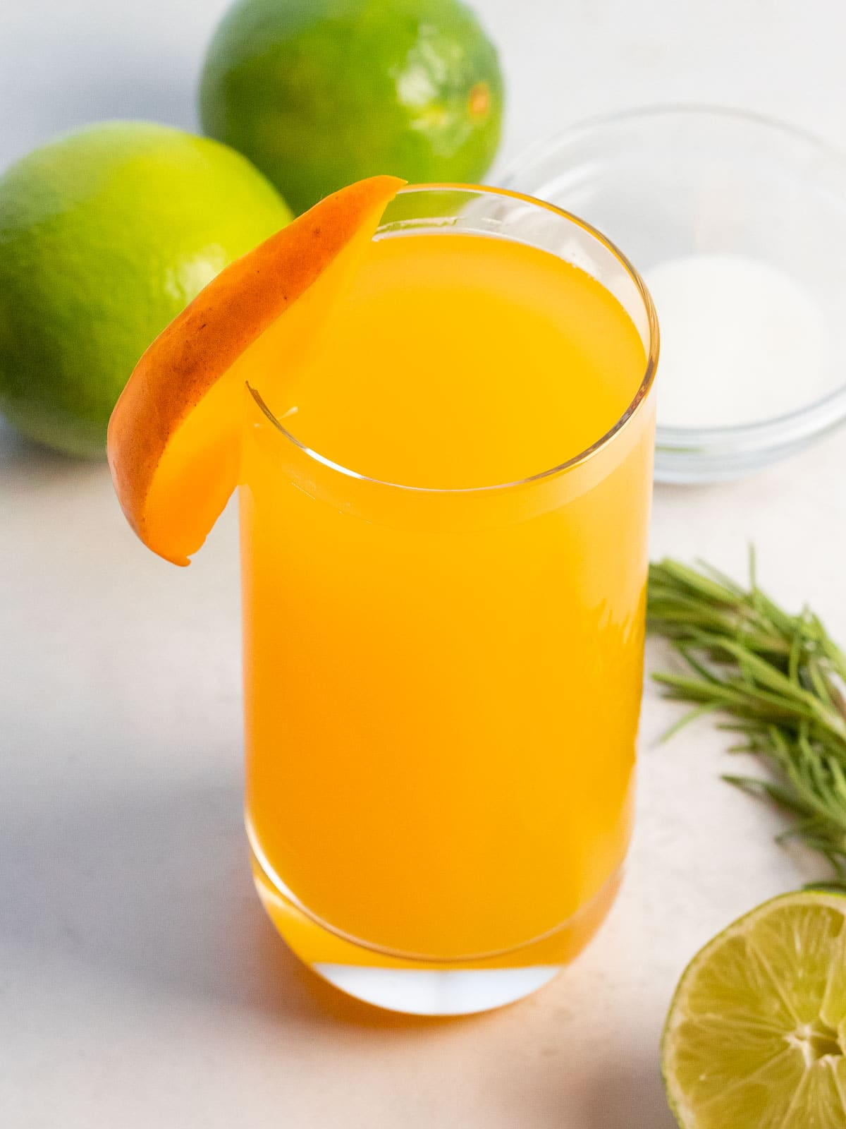 glass of mango agua fresca with a slice of mango garnish with limes