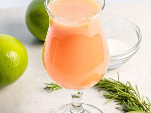 peach agua fresca in a glass next to limes