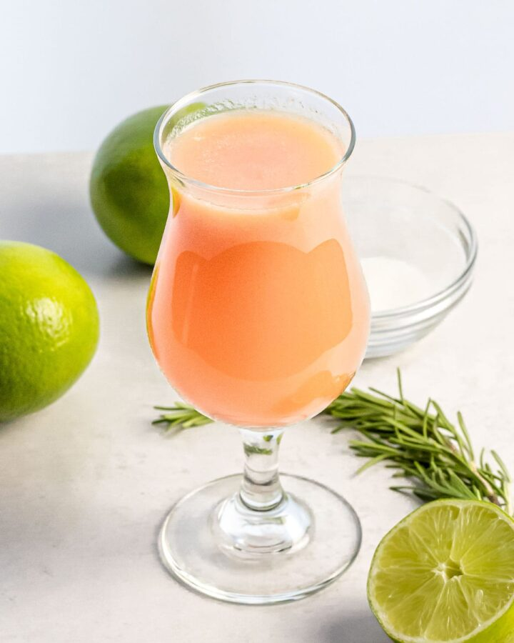 glass of peach agua fresca next to limes and herbs