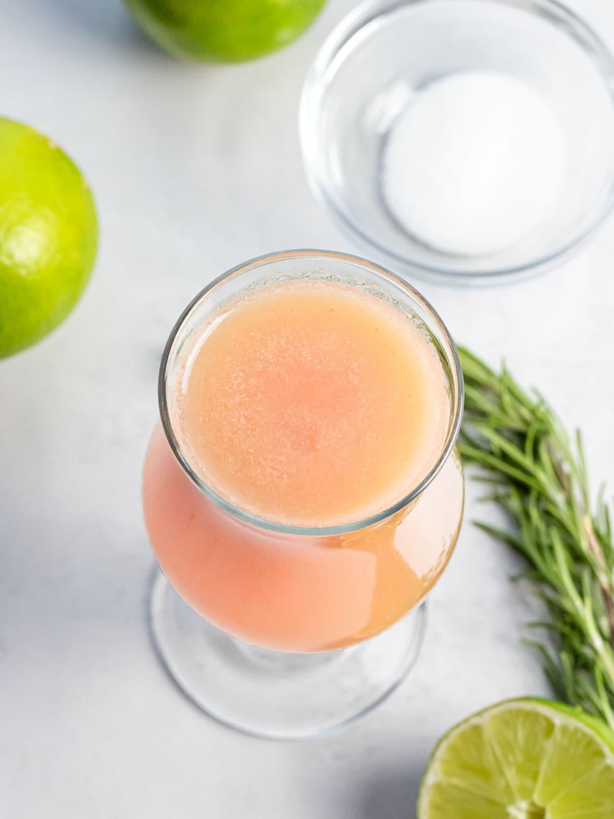 white peach agua fresca in a glass next to lime, sugar, and herbs