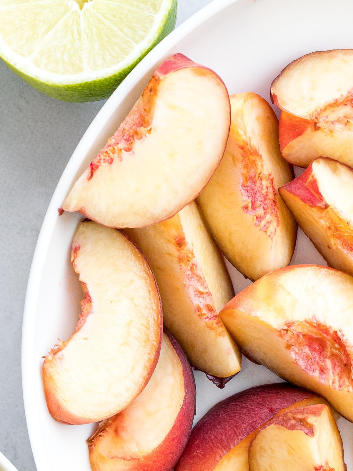 slices of white peaches next to lime