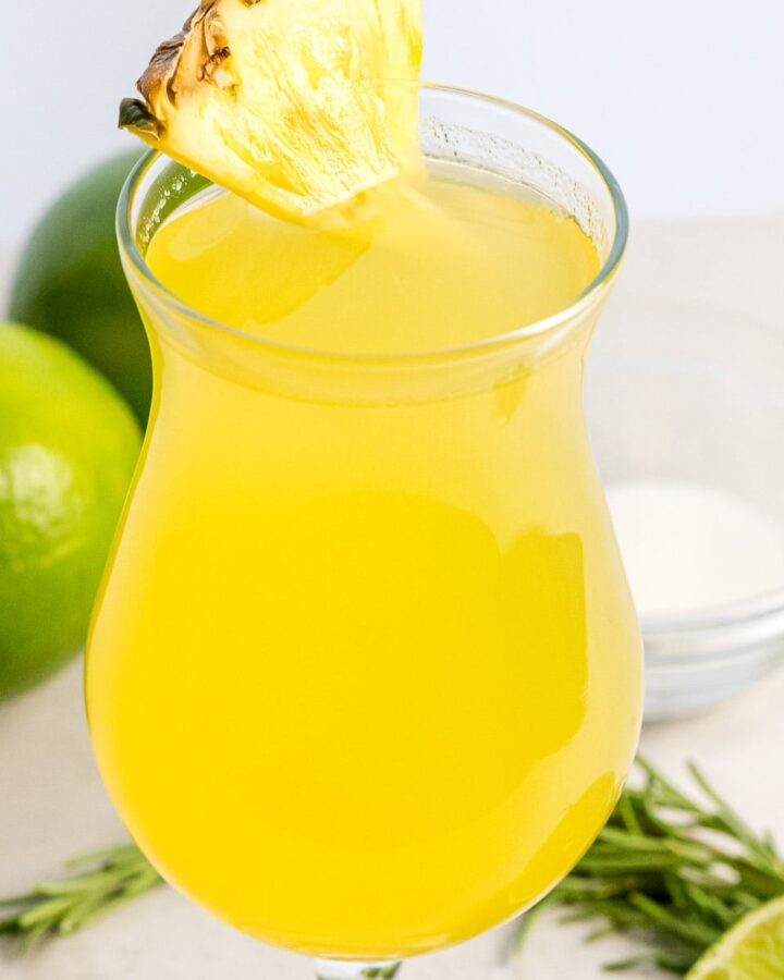 close up of pineapple agua fresca with a slice of pineapple next to lime
