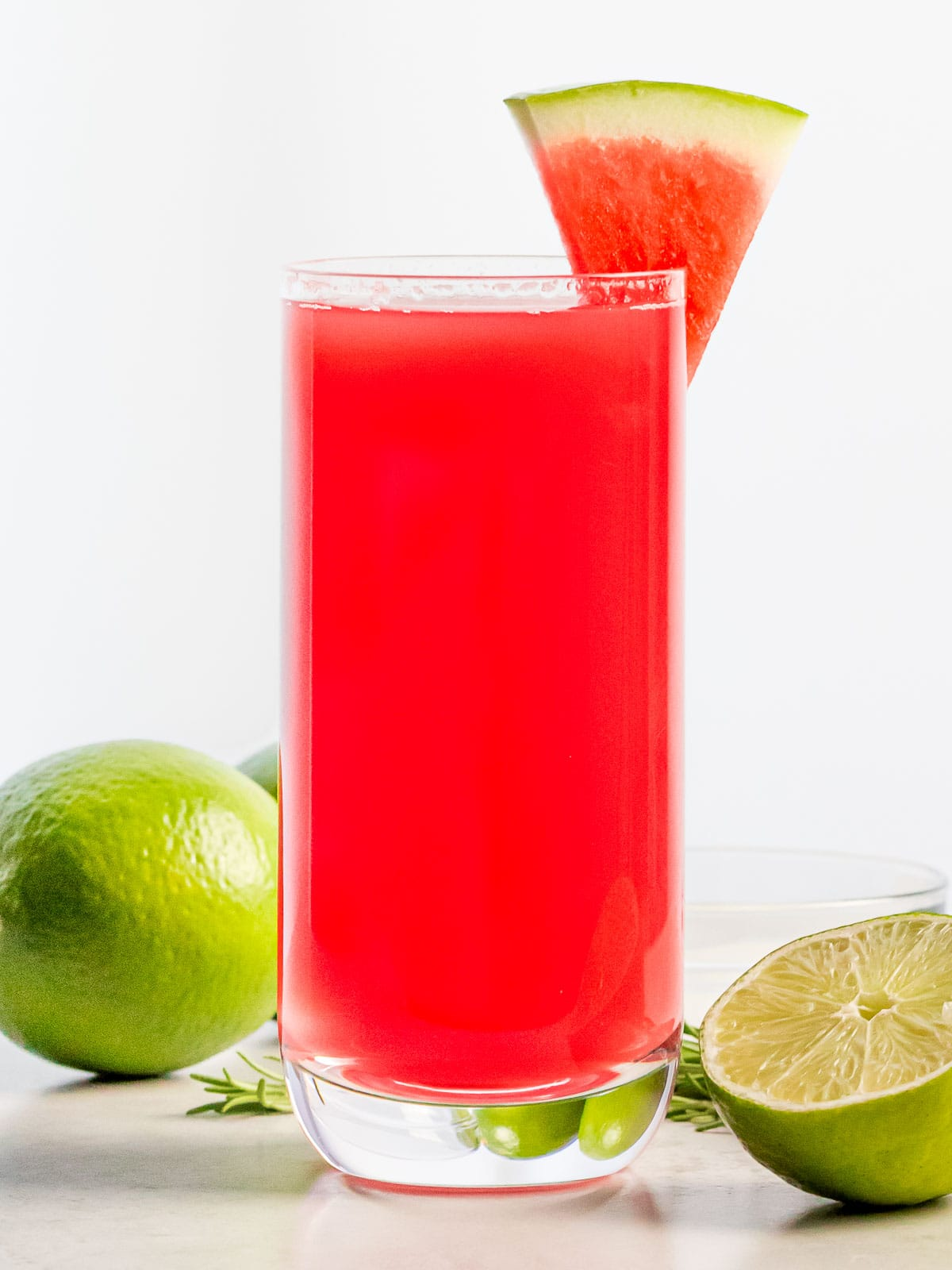 glass full of watermelon agua fresca with a slice of watermelon next to lime
