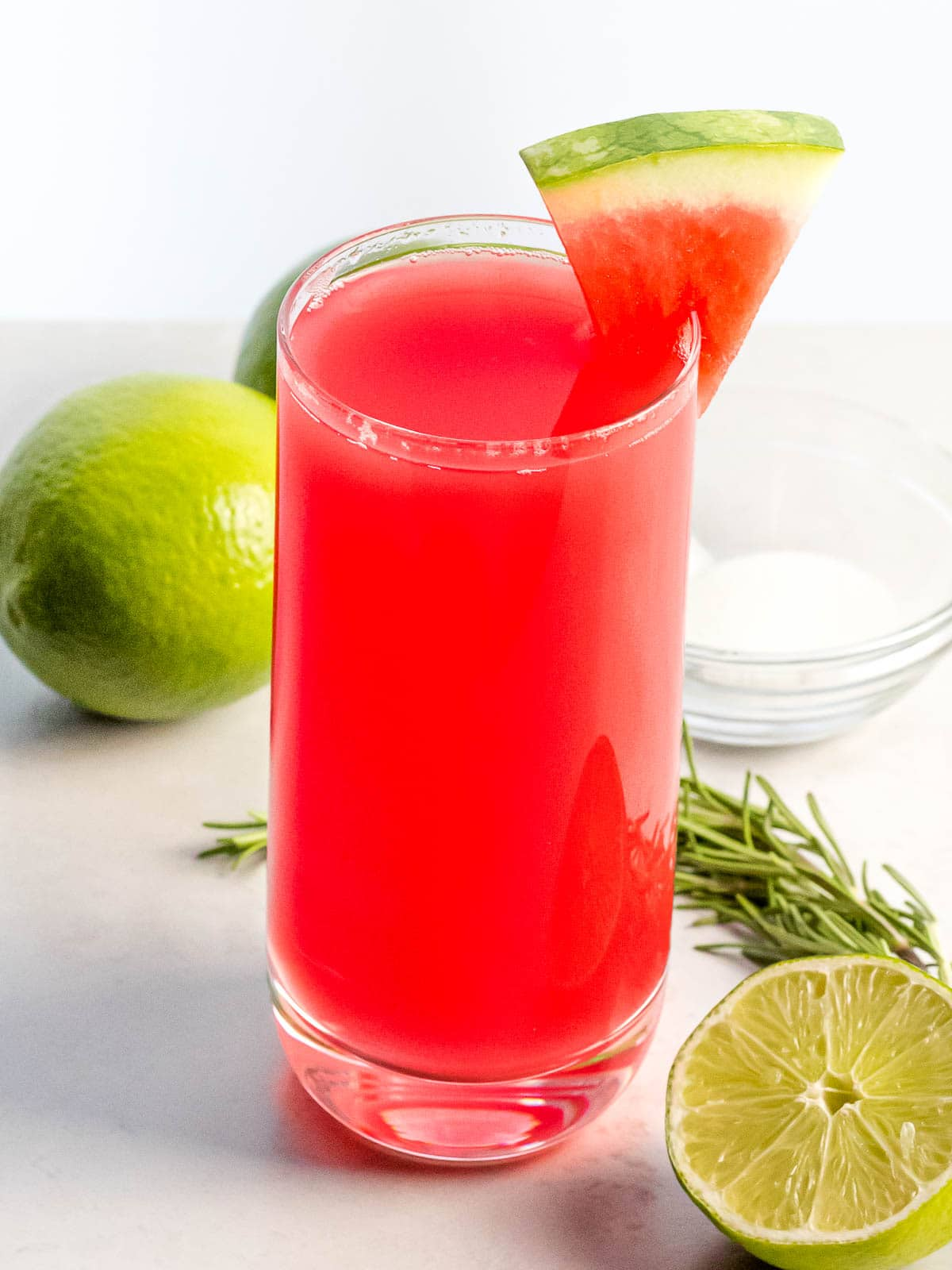 a glass of watermelon agua fresca with a piece of watermelon next to lime and herbs