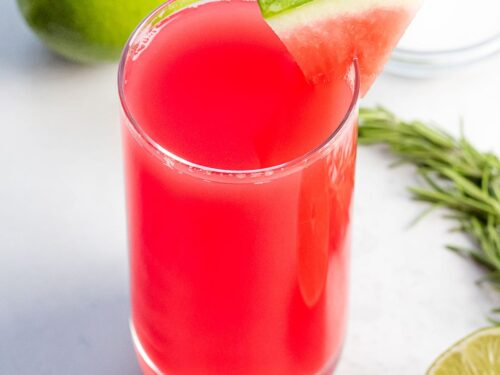 watermelon agua fresca with a piece of watermelon next to lime