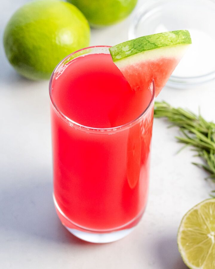 watermelon agua fresca in a glass cup with lime and herbs