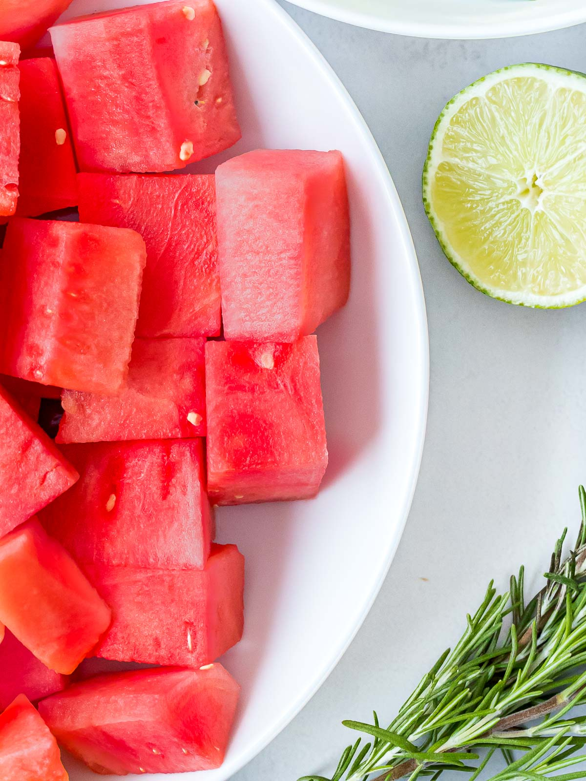 watermelon cut into pieces next to a lime and herbs
