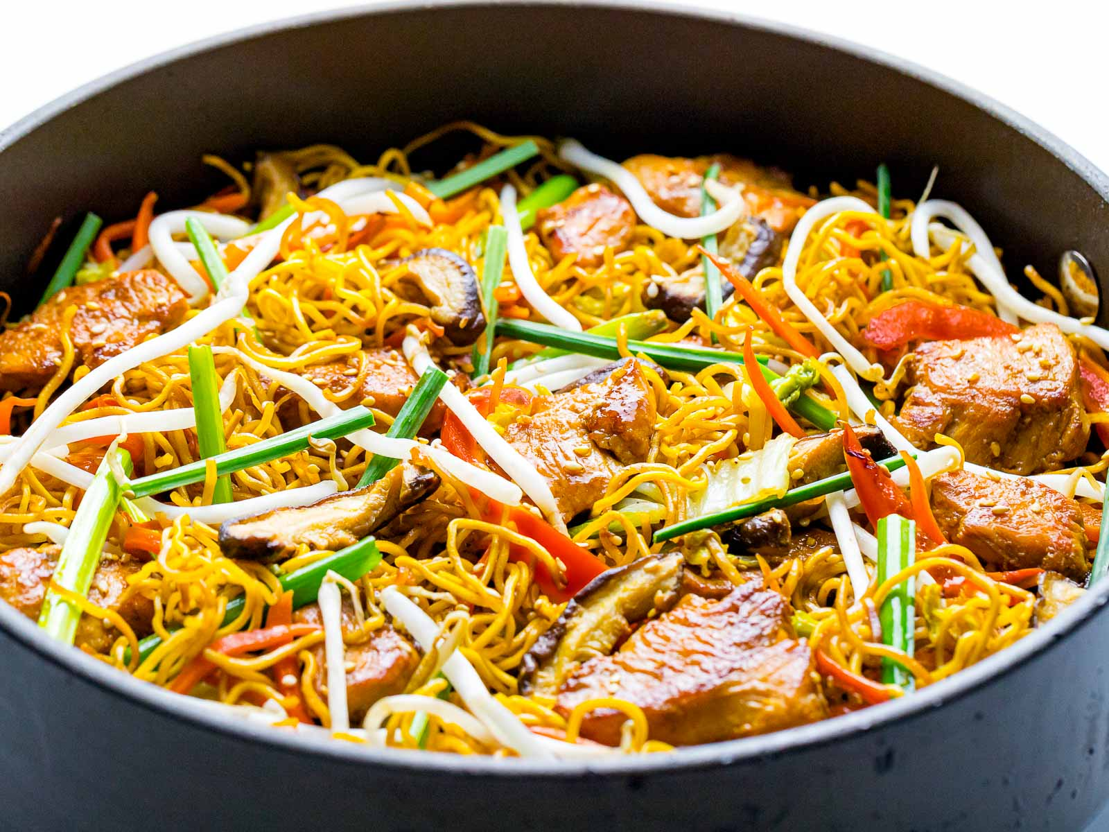 chicken chow mein with vegetables and bean sprouts in a pan