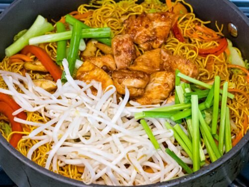 chow mein noodles with bean sprouts, chicken, chives, and red peppers in a pan