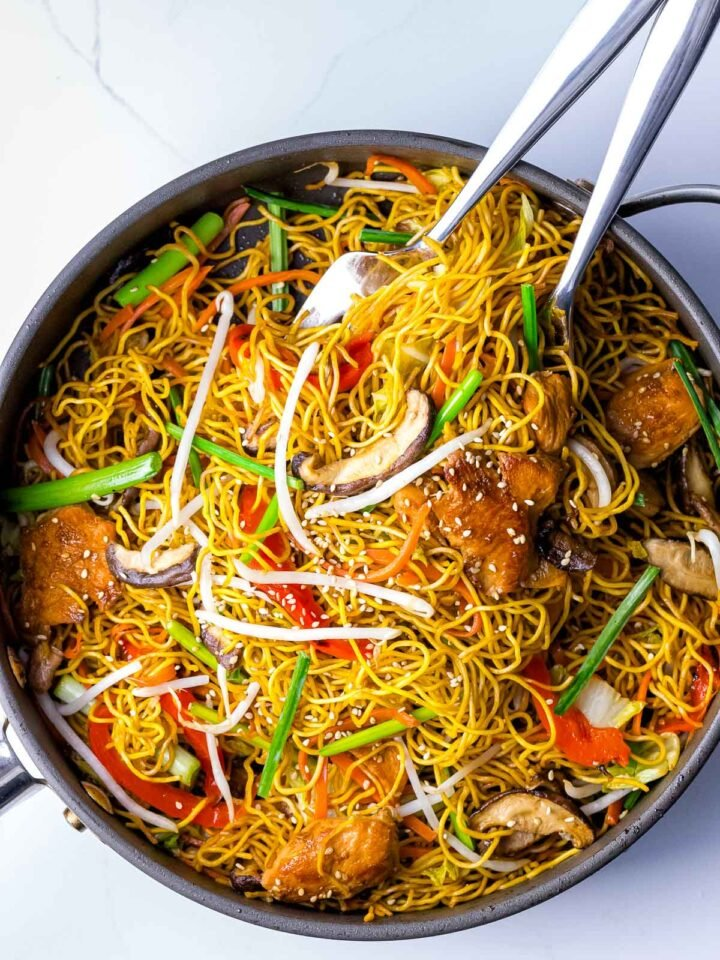 chicken chow mein noodles with vegetables and bean sprouts with serving utensils in the pan