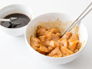 chicken breast mixed with soy marinade in a white bowl