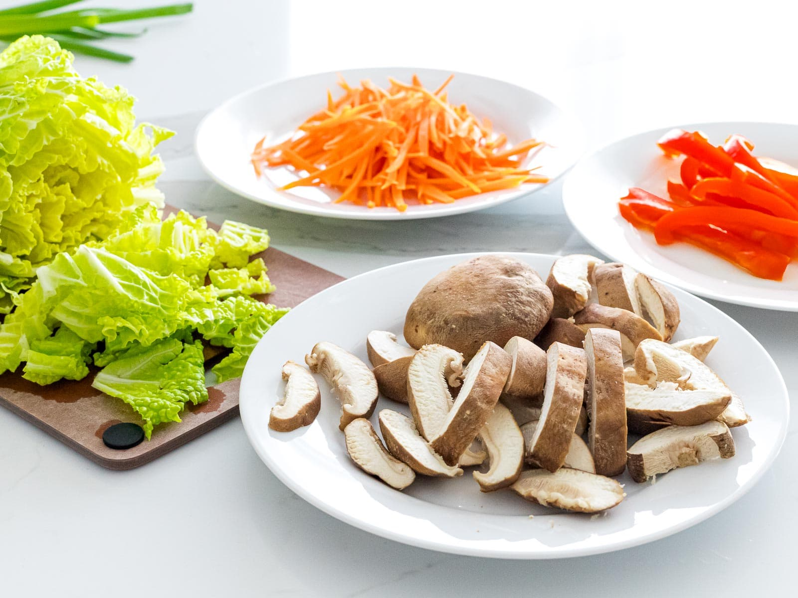 sliced shiitake mushrooms, chopped cabbage, julienned carrots and red peppers on white plates
