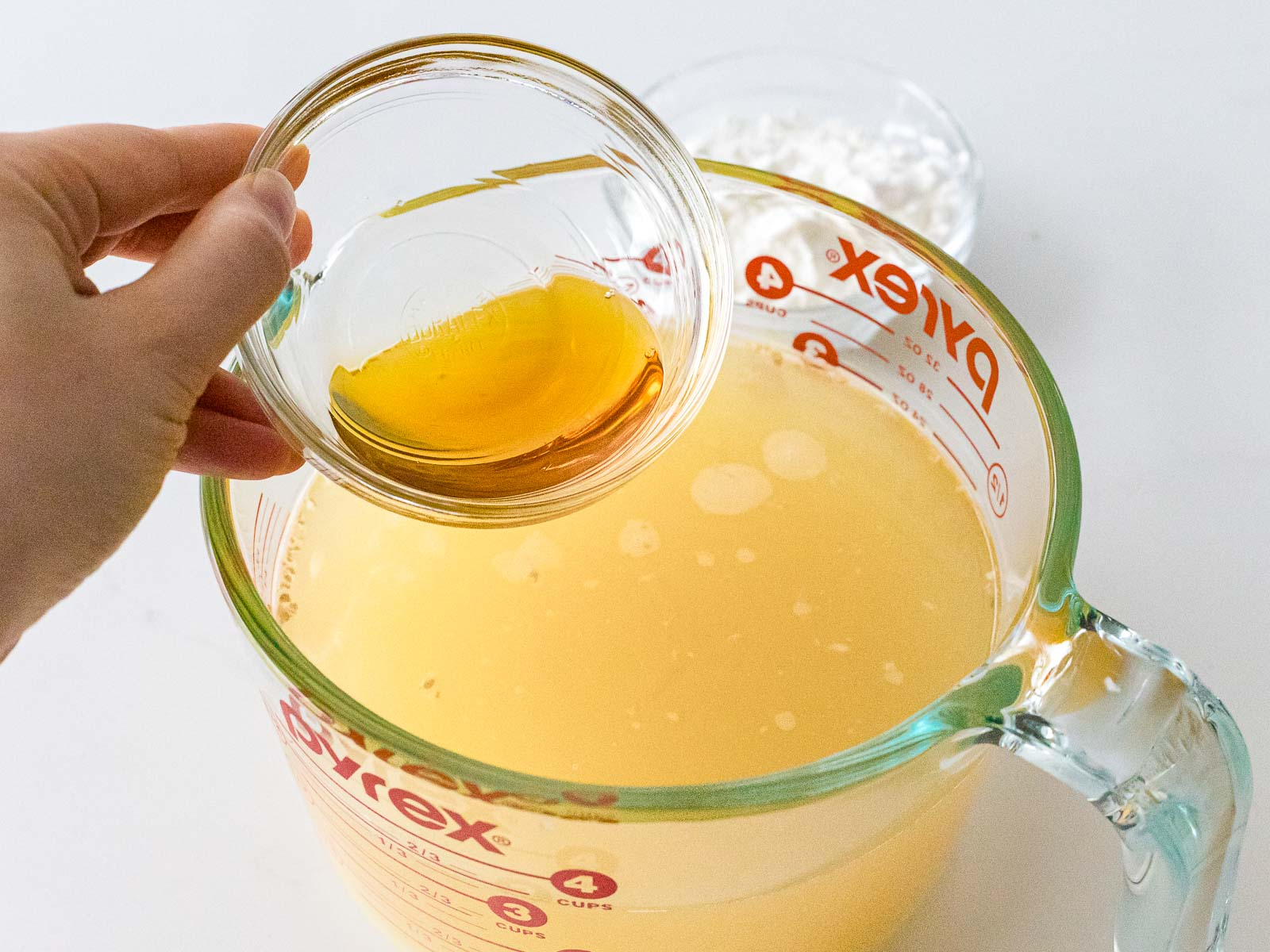 sesame oil added to stock in a glass measuring cup