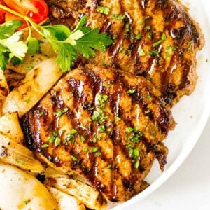 juicy grilled pork chops with a savory marinade next to onions and tomatoes