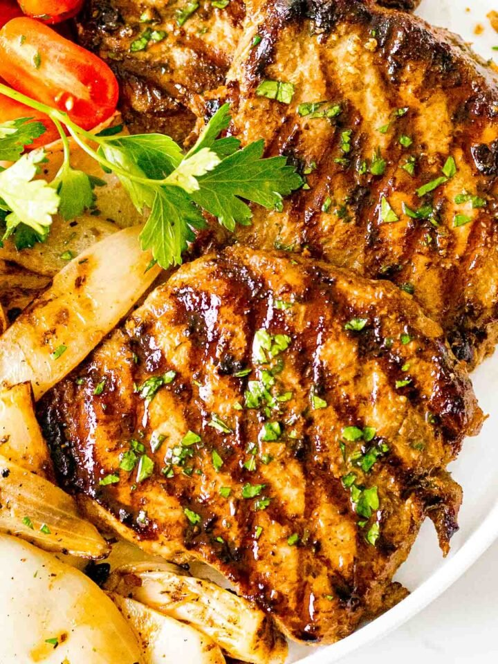 juicy grilled pork chops with savory marinade on a white plate with tomatoes and onions