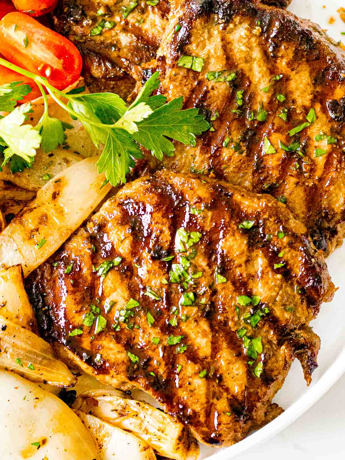 easy juicy grilled pork chops with savory marinade on a white plate with tomatoes and onions
