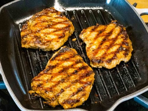 juicy grilled pork chops with grill marks in a pan