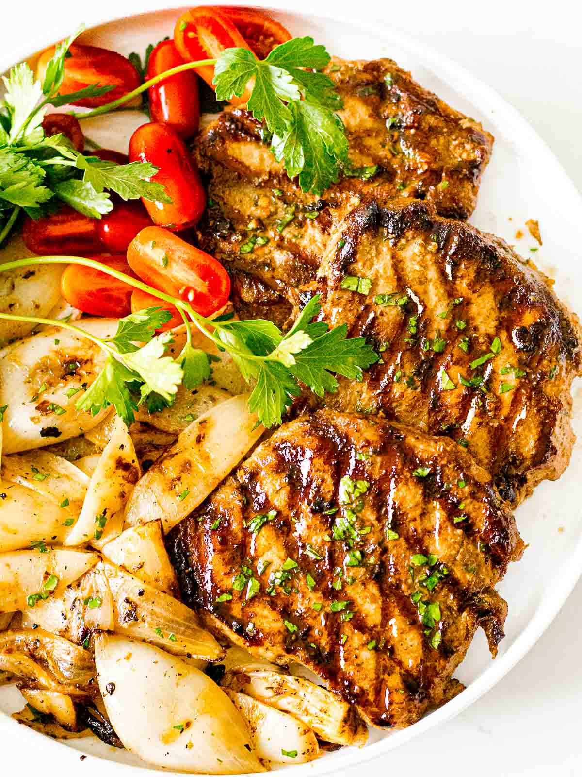 juicy grilled pork chops with grill marks on a white plate next to grilled onions and tomatoes