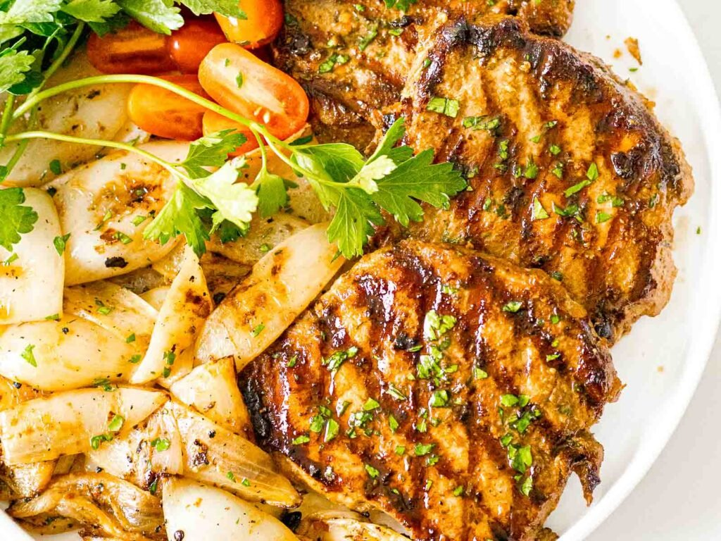savory grilled pork chops on a white plate next to grilled onions and tomatoes