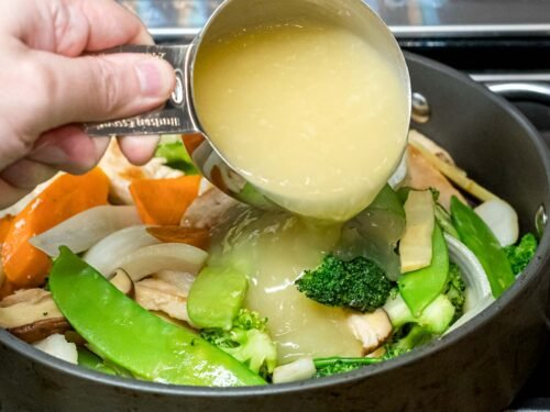 Moo goo gai pan sauce being added to chicken and vegetables stir fry