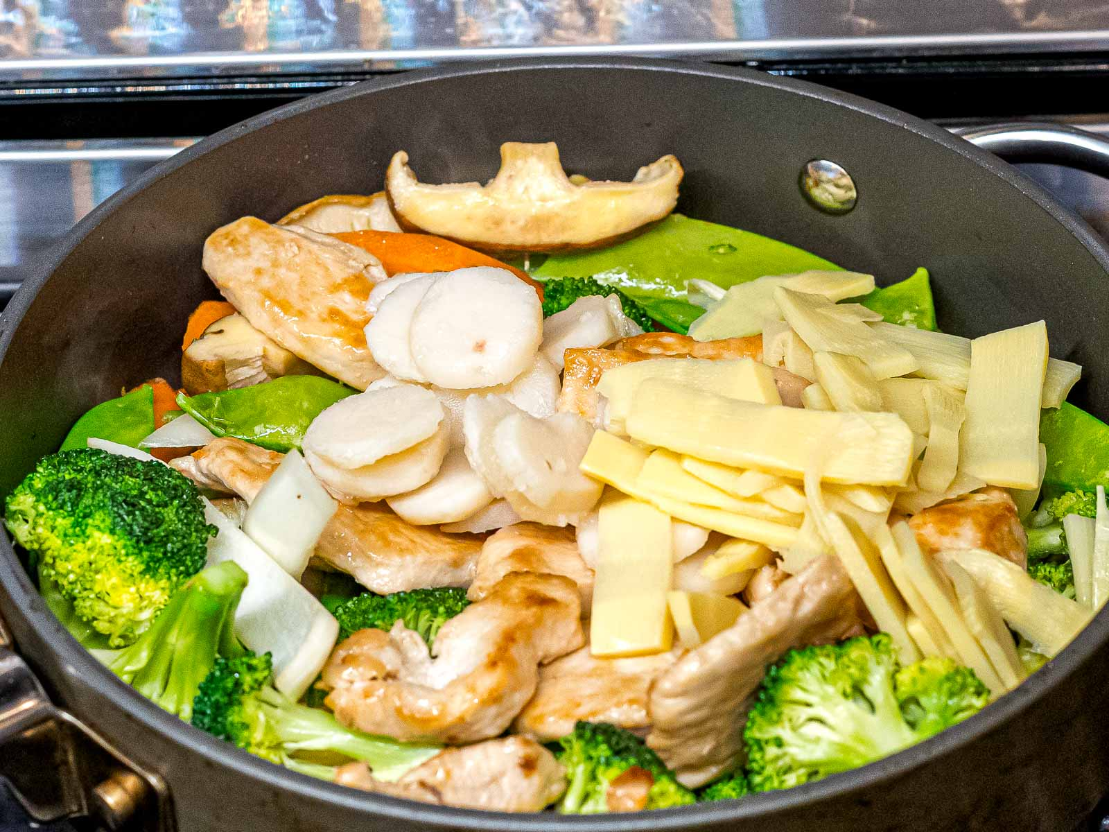 chicken, mushrooms, bamboo shoots, water chestnuts stir frying in a pan