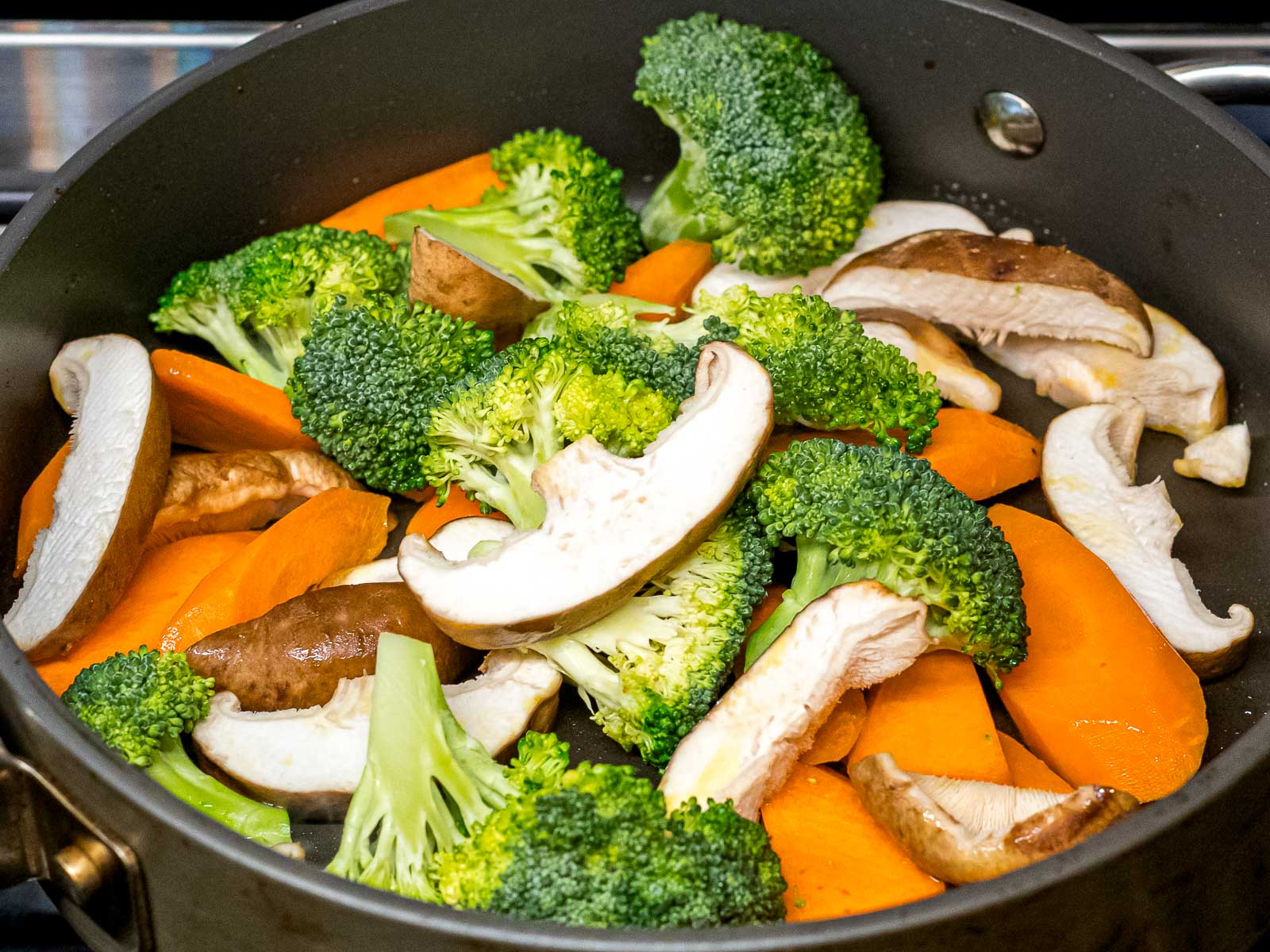 mushroom, broccoli, and carrots stir fried in a pan