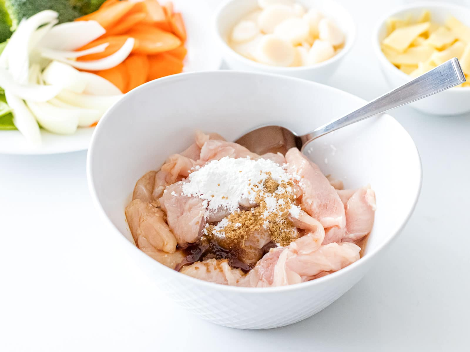 chicken breast marinating in a white bowl next to vegetables