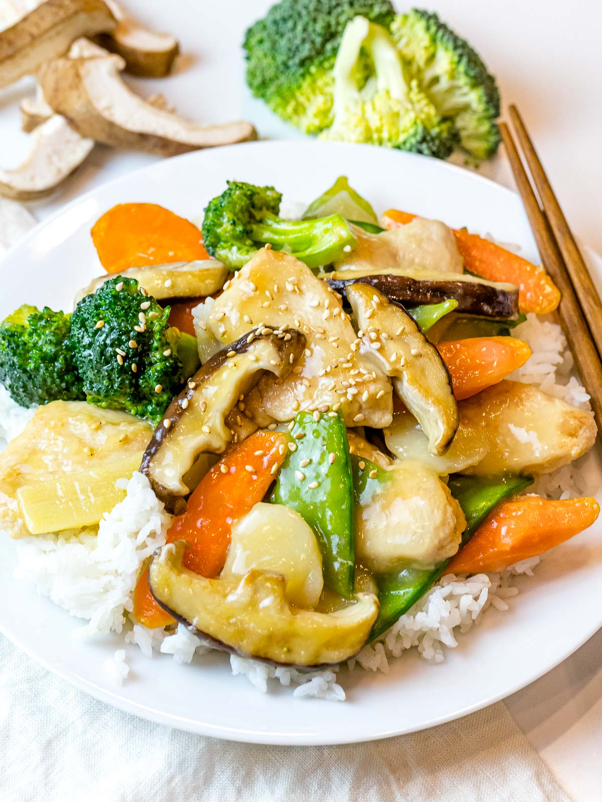 Chinese moo goo gai pan stir fry on a plate of rice next to chopsticks