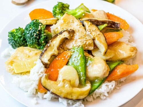moo goo gai pan served on top of white rice with sesame seeds