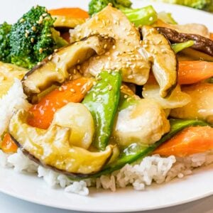 moo goo gai pan with chicken, mushrooms, and vegetables on a plate of white rice