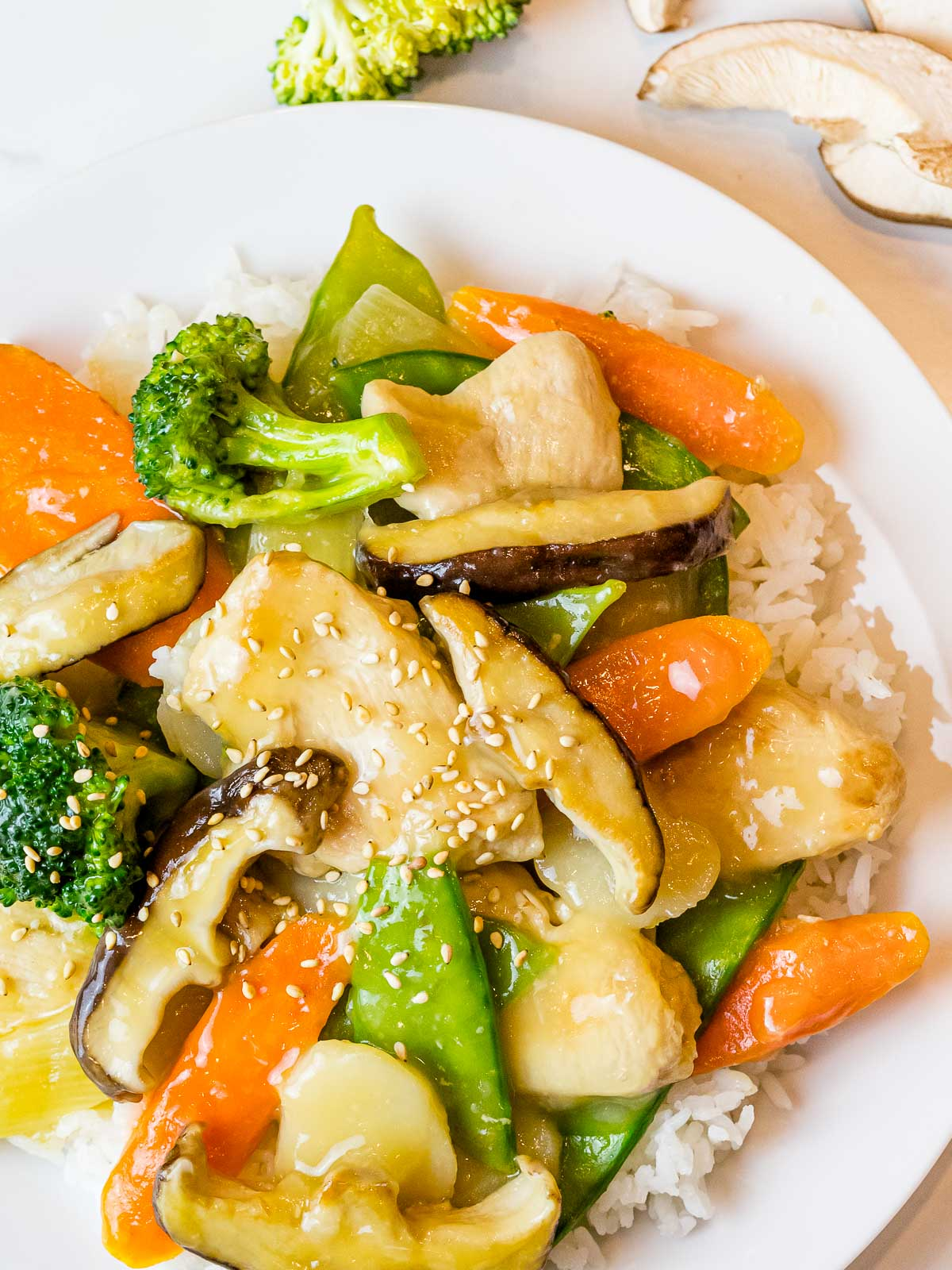 Chinese mushroom chicken stir fry with broccoli and carrots on a plate of rice