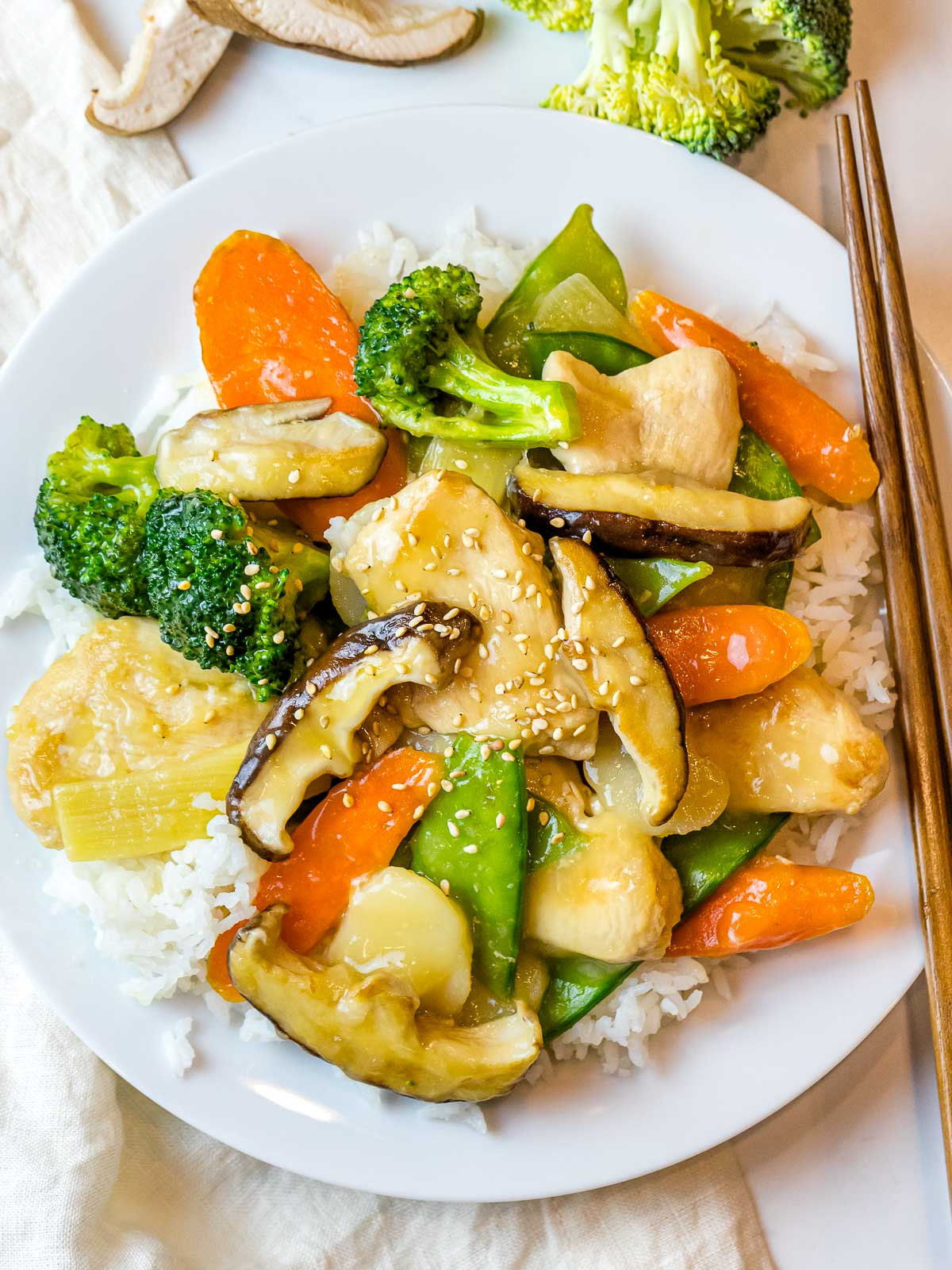 moo goo gai pan with rice on a white plate next to chopsticks