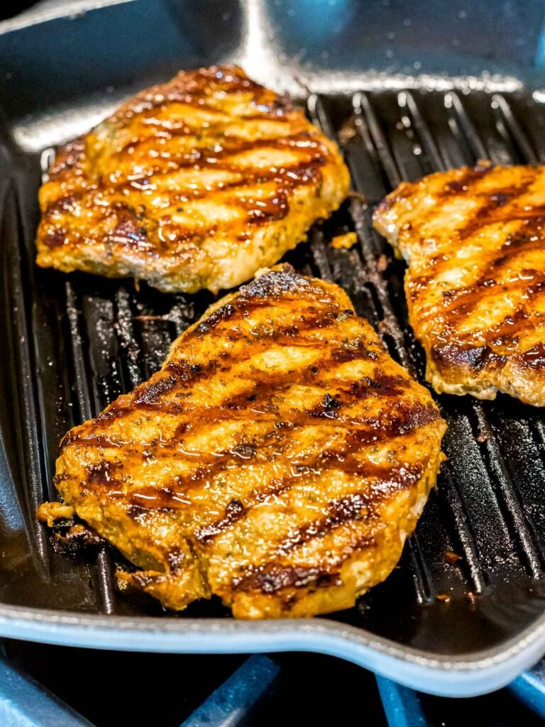 three grilled pork chops with grill lines in a pan