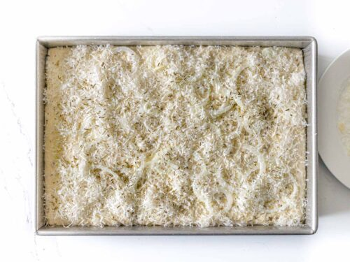 focaccia dough topped with parmesan cheese, onions, and rosemary in a baking dish