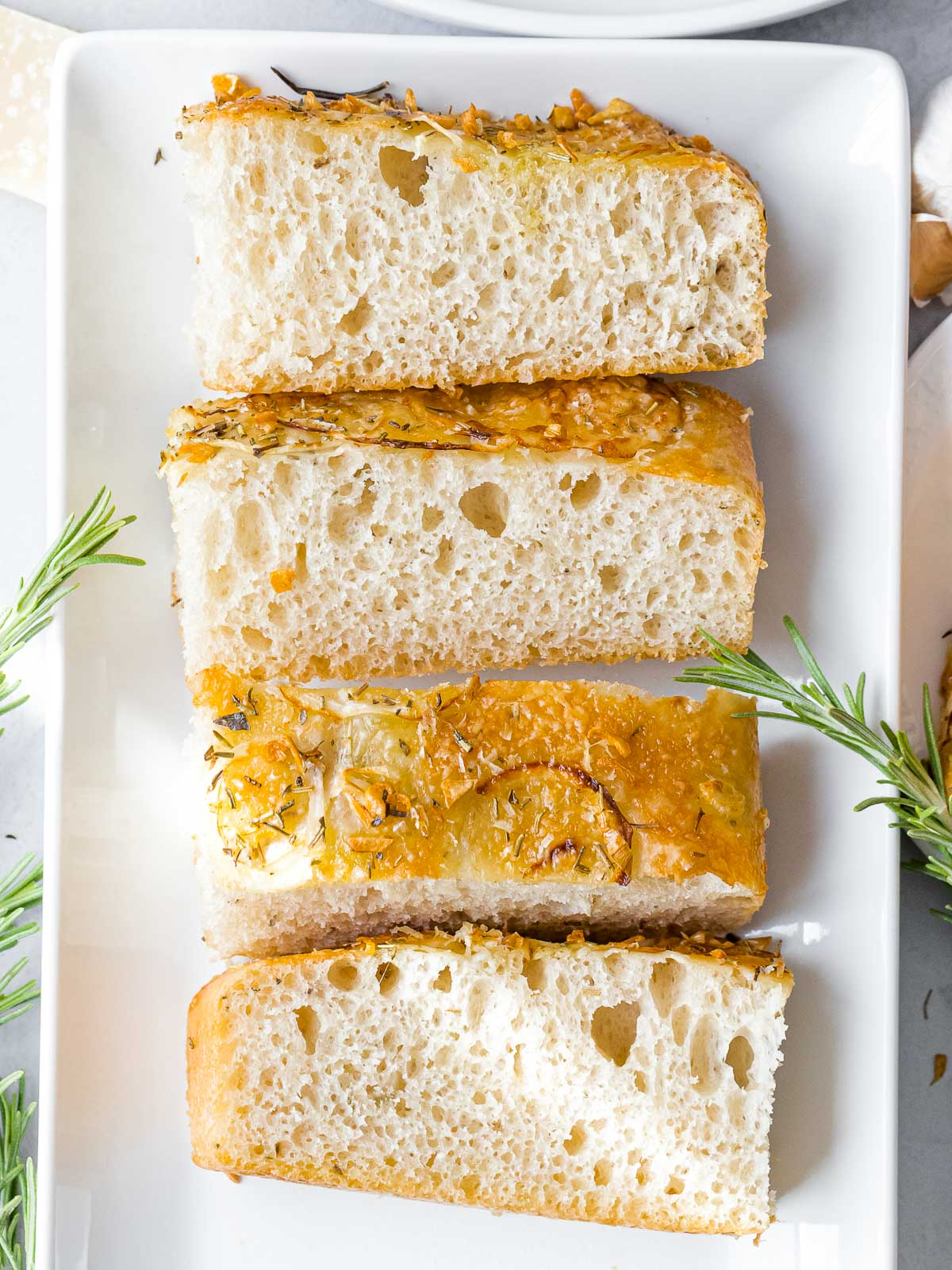slices of sourdough focaccia bread on a white plate next to rosemary