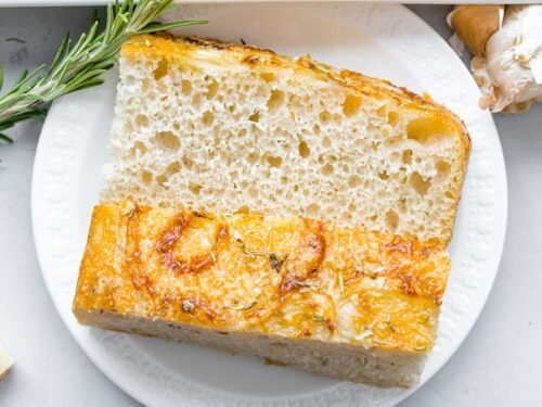 slice of rosemary parmesan focaccia bread on a white plate next to rosemary and garlic