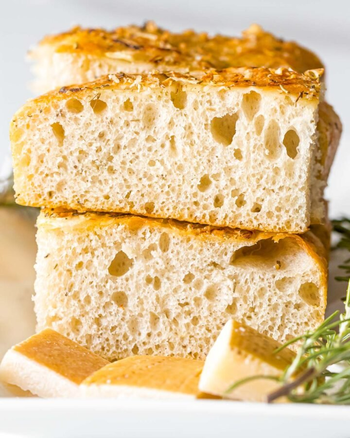slices of sourdough focaccia bread stack on top of each other next to rosemary and parmesan