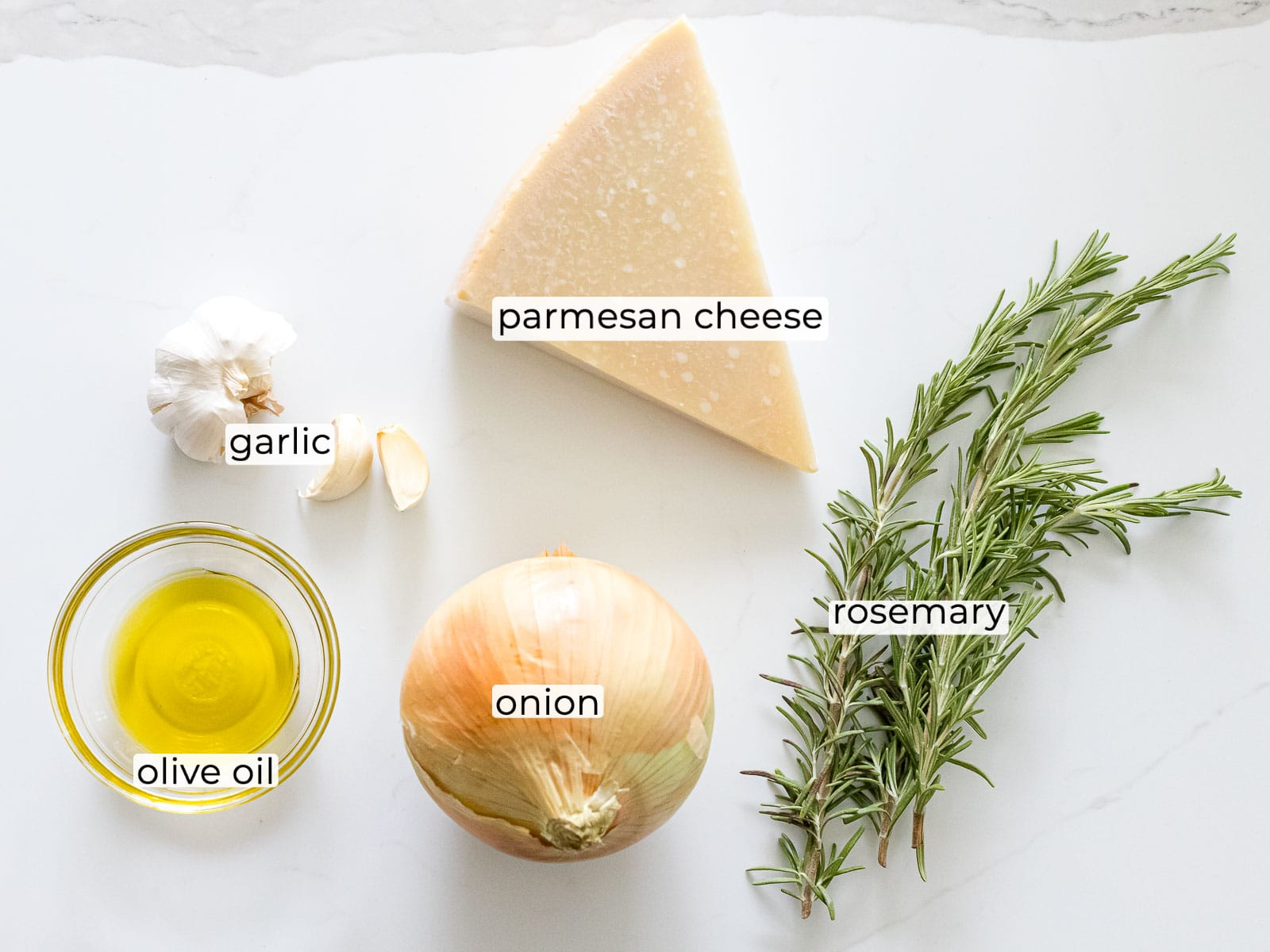 a block of parmesan cheese with rosemary, onion, olive oil, and garlic