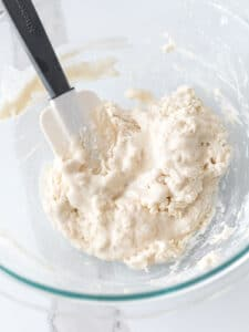 water and flour mixture combined with a spatula in a glass bowl