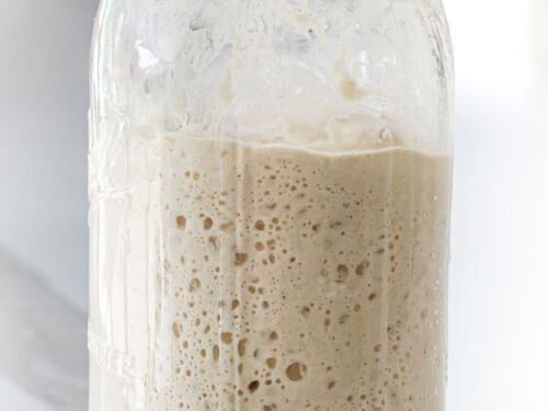 active sourdough starter in a glass mason jar showing bubbles and increase in volume
