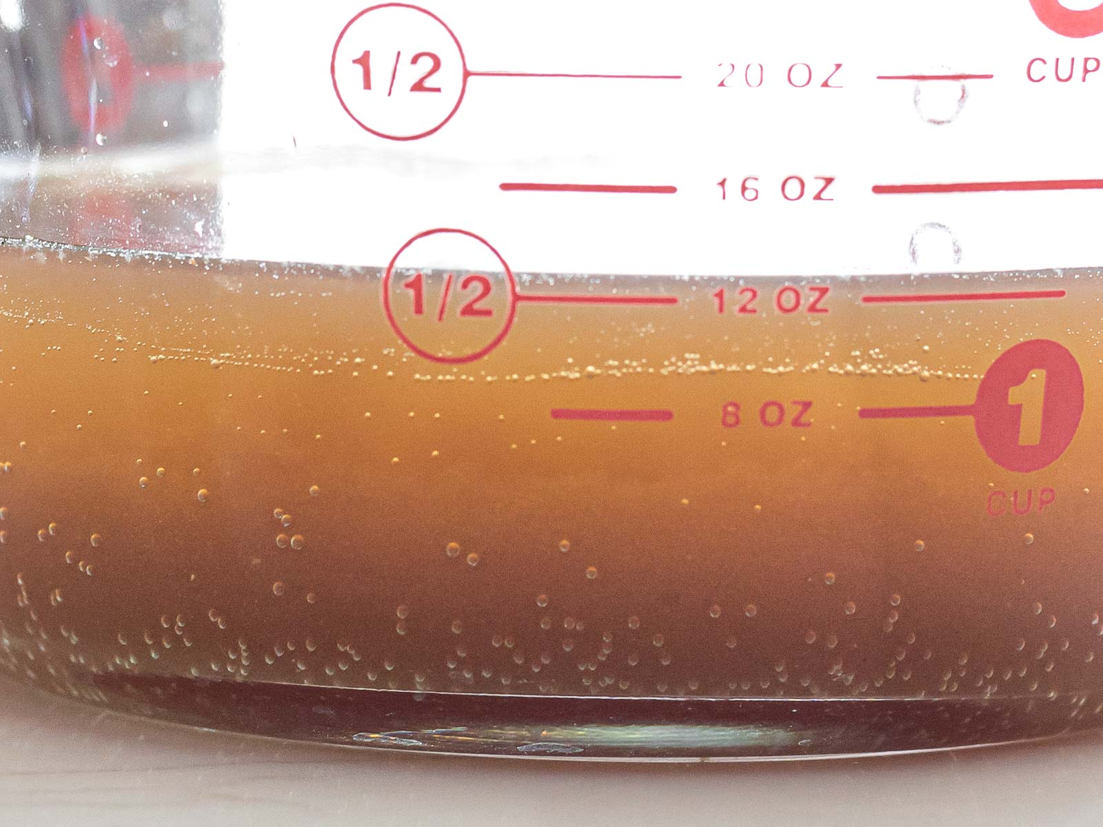 close up of fermented yeast water in a glass measuring cup