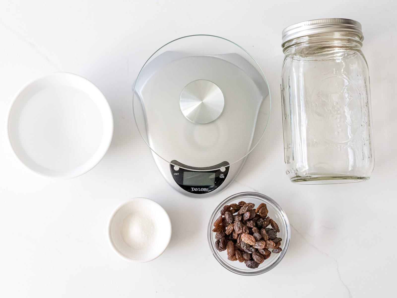 ingredients for raisin yeast water including raisins, kitchen scale, mason jar, water, and sugar