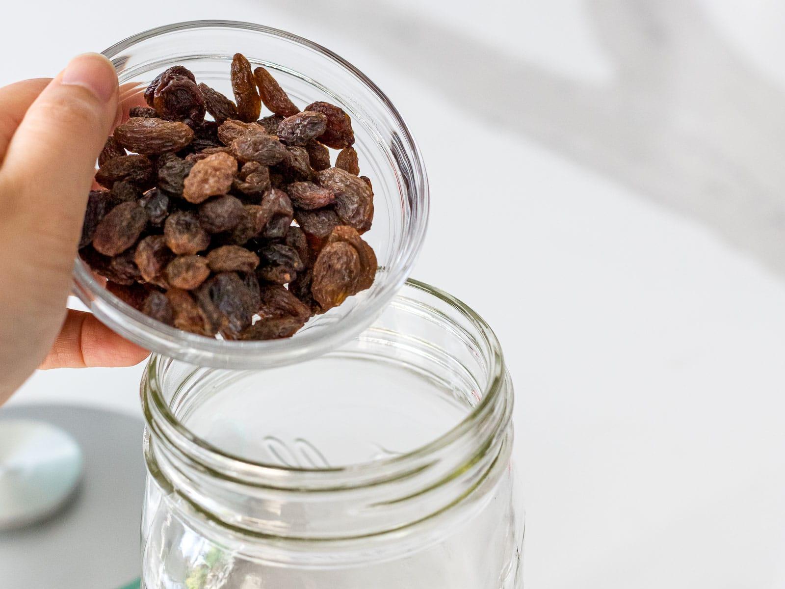 raisins being added to a glass mason jar