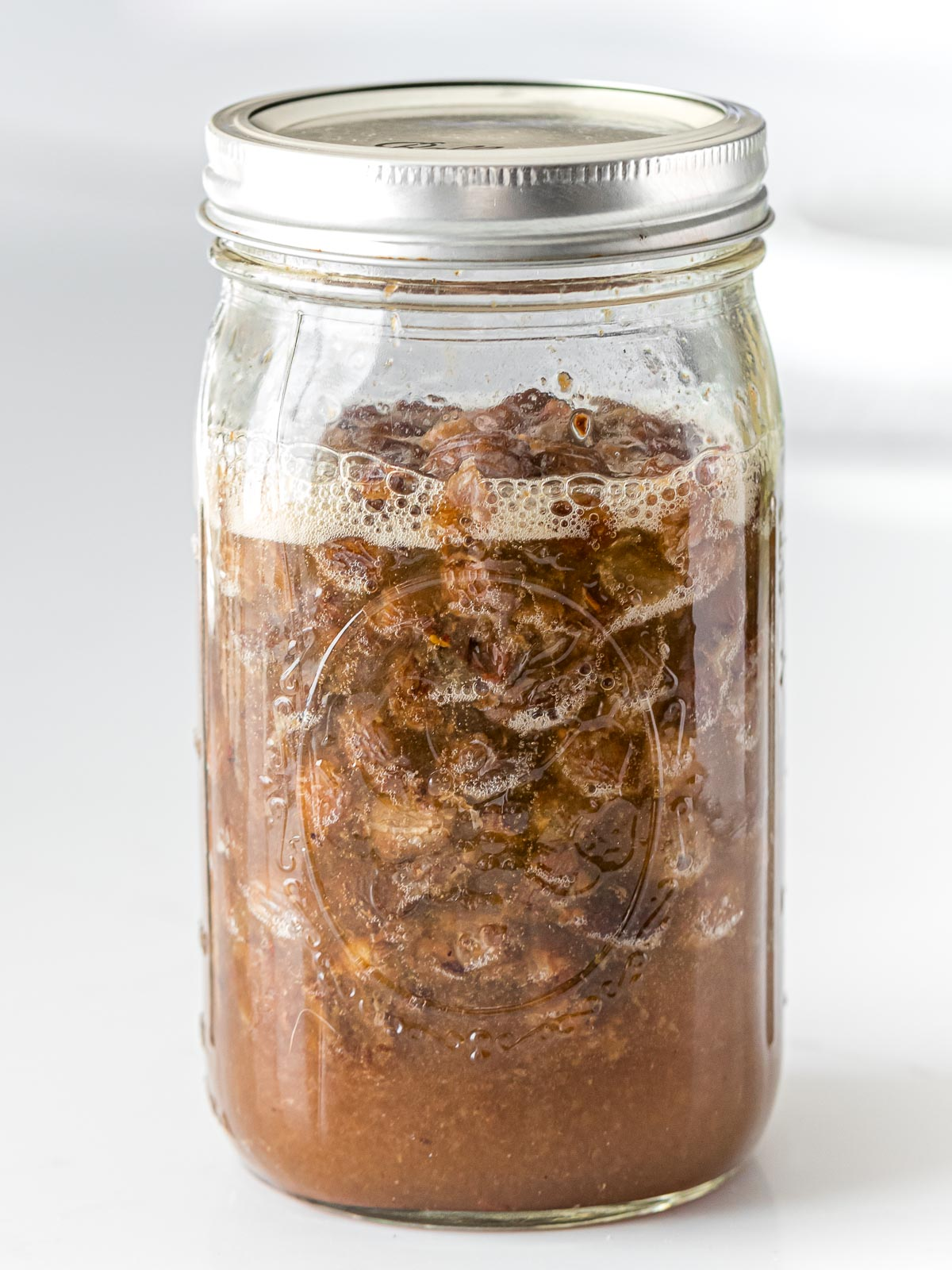 raisin yeast water with bubbles and foam in a glass mason jar with a lid