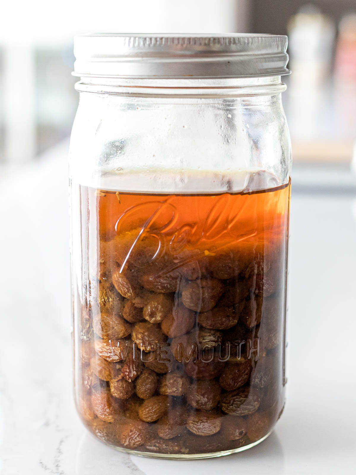 raisins sitting in water inside a glass mason jar with a screw top lid