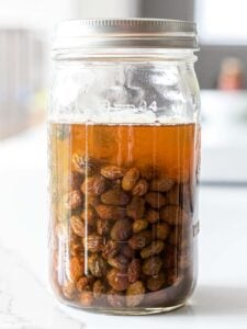 raisin yeast water in a mason glass jar on a white counter top